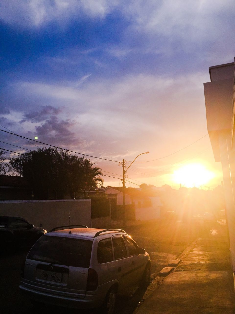 car, sunset, transportation, sky, land vehicle, cloud - sky, no people, mode of transport, built structure, building exterior, architecture, sunlight, road, outdoors, city, day