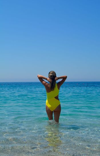Rear view of woman standing in sea against clear blue sky