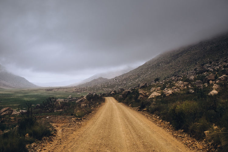 The road less taken Cloudy Beauty In Nature Cloud - Sky Diminishing Perspective Direction Dirt Dirt Road Environment Landscape Long Mountain Nature No People Non-urban Scene Outdoors Overcast Road Scenics - Nature Sky The Way Forward Tranquil Scene Tranquility Transportation vanishing point