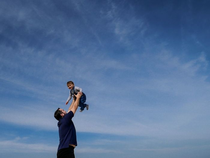 Low angle view of father holding cute baby son while standing against blue sky