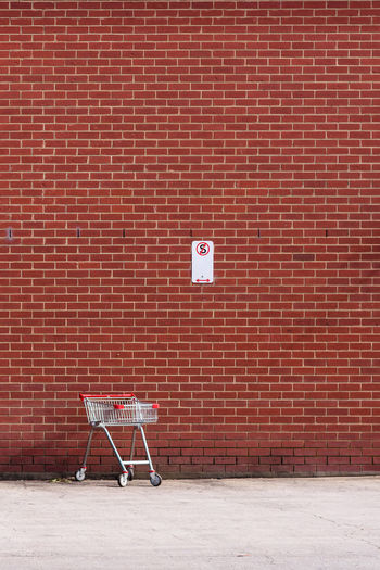 A lonely shopping trolley stays in a non-stoping open space, against a red brick wall.