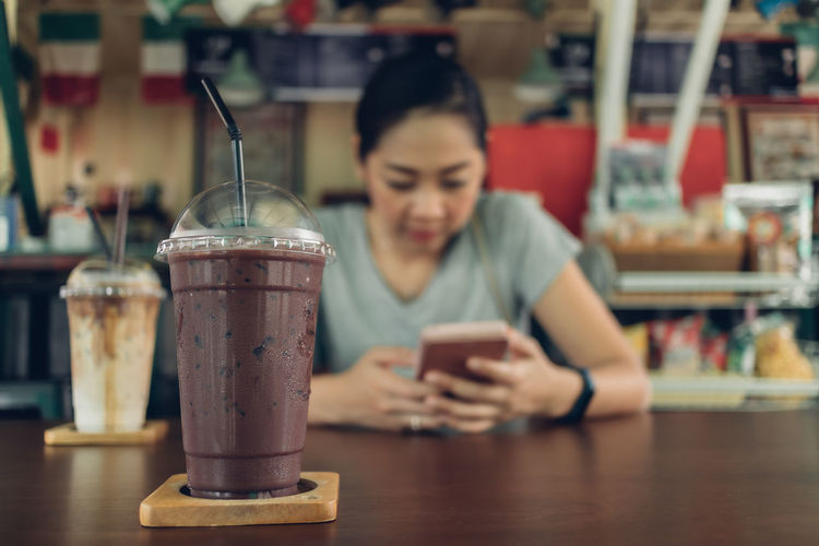 Midsection of woman using smart phone at cafe