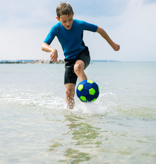 Full length of boy playing soccer ball in water at beach