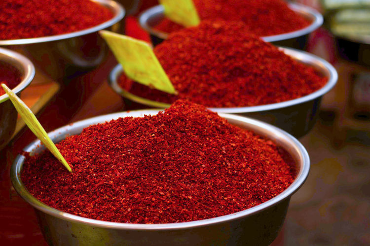 High angle view of red chili powder in bowls