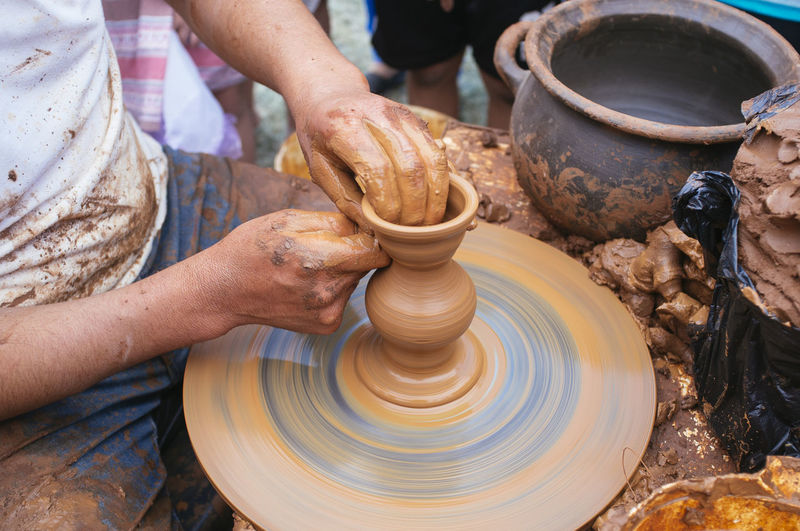 Close-Up Of Man Shaping Pottery Clay On Wheel