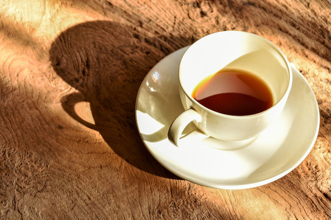 Half cup of coffee in afternoon sunlight on wood background. Afternoon Light Coffee Time Afternoon Coffee Background Close-up Coffee - Drink Coffee Break Coffee Cup Drink Food And Drink Freshness Half Cup Of Coffee Refreshment Saucer Shadow Table White Cup Wooden