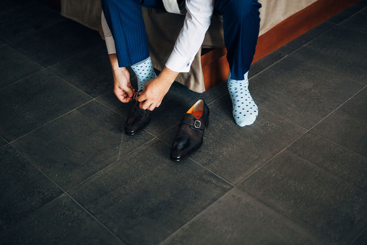 Low section of man wearing shoes at home