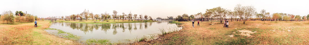 tree, water, nature, outdoors, day, tranquil scene, tranquility, grass, lake, scenics, no people, panoramic, beauty in nature, sky, building exterior
