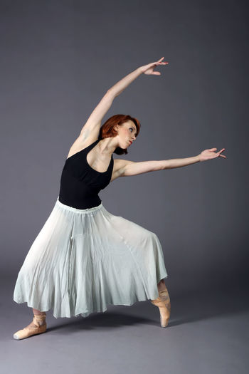 Ballet Dancer Dancing Against Gray Background