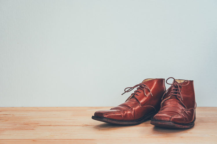 High angle view of shoes on hardwood floor against wall