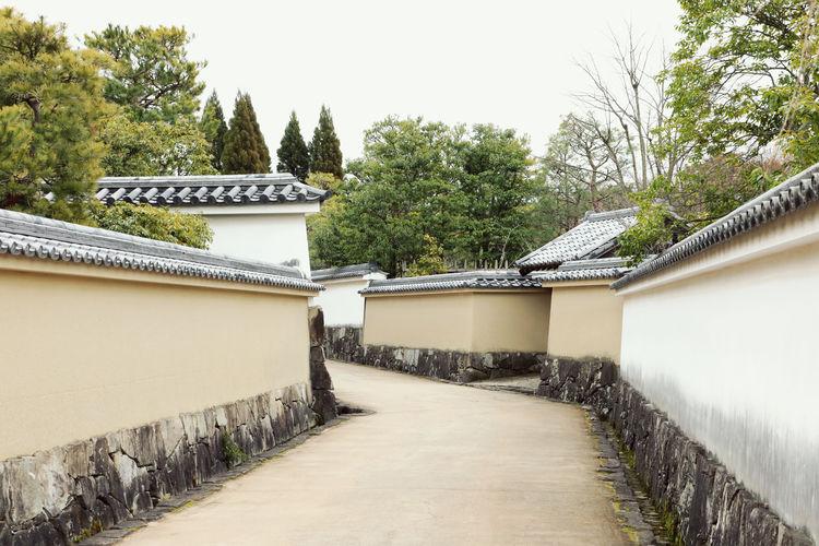 Walkway by building against sky