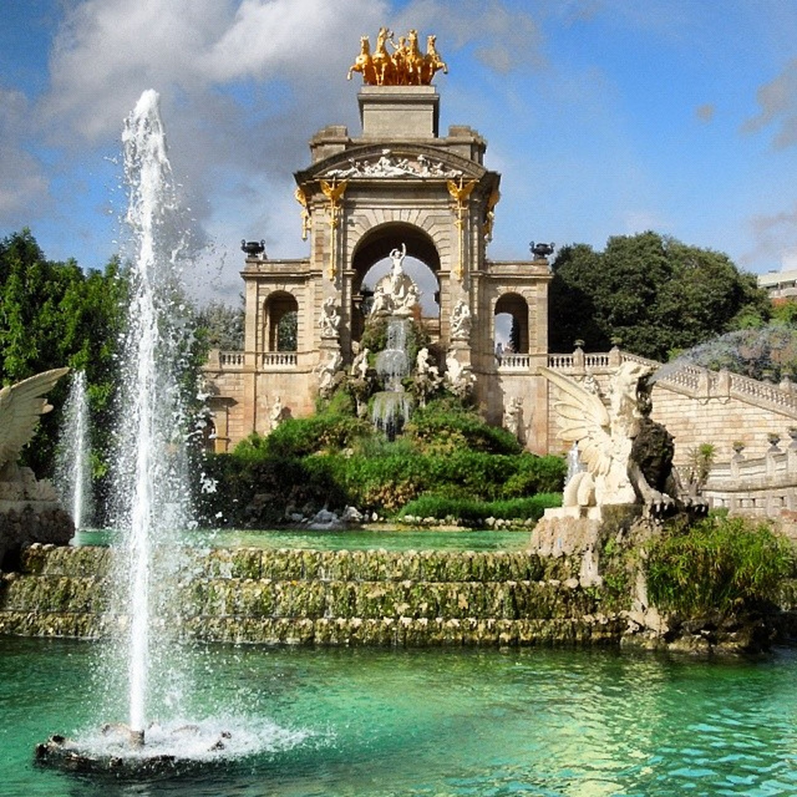 water, fountain, architecture, built structure, building exterior, sky, statue, sculpture, famous place, travel destinations, tree, motion, art, art and craft, history, splashing, waterfront, tourism, travel, arch