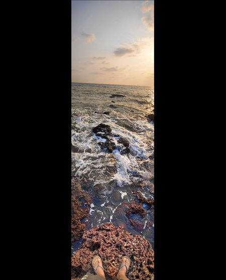 Digital composite image of rocks in sea during sunset