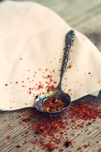 Crushed Red Peppers On Vintage Spoon By Fabric At Table
