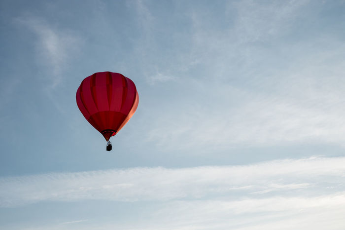 Hot air balloon in the sky Summertime Adventure Air Vehicle Balloon Cloud - Sky Day Extreme Sports Flying Freedom Hot Air Balloon Leisure Activity Low Angle View Mid-air Parachute Paragliding Parasailing Red Sky Sport Transportation Unrecognizable Person