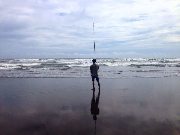 Rear View Of Man With Fishing Rod Standing On Shore At Beach Against Cloudy Sky