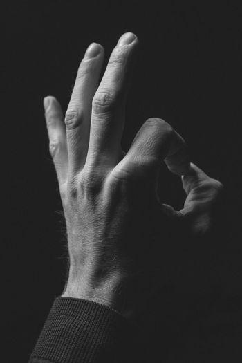 Close-up of man hand gesturing ok sign against black background