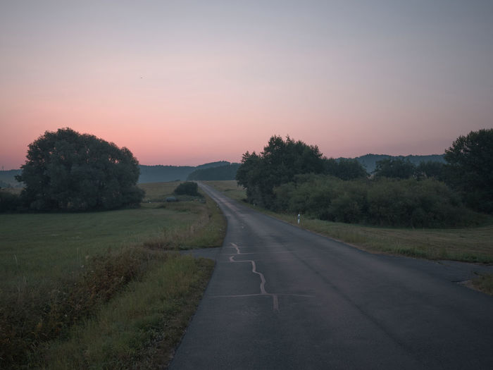 Empty road amidst field against sky during sunset