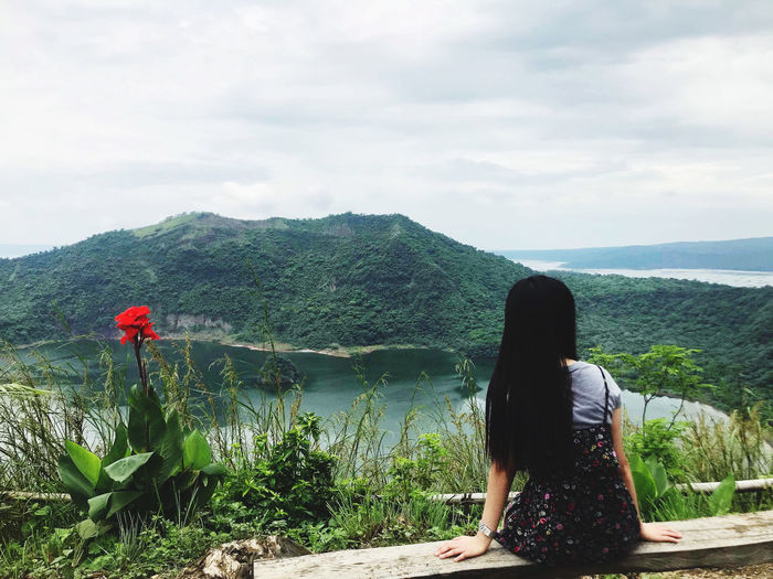 Rear view of woman looking at taal volcano