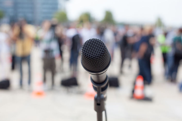 Close-Up Of Microphone Against Crowd