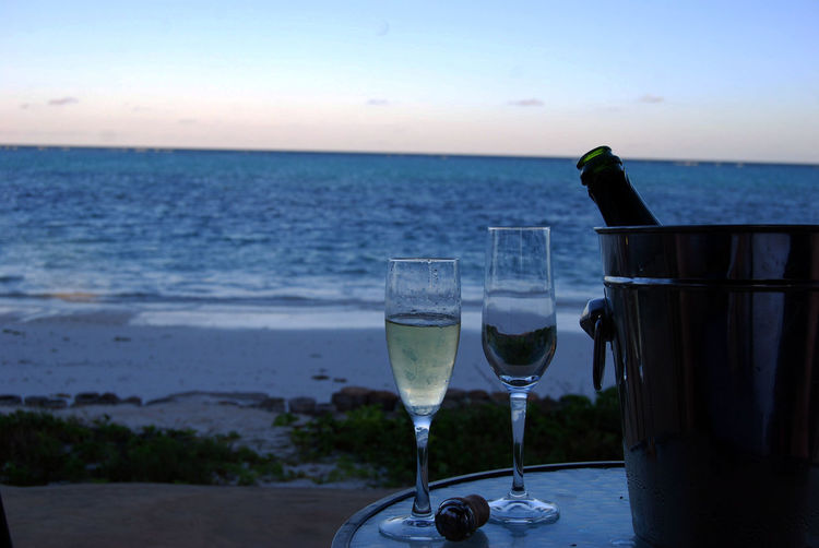 Close-up of champagne on beach against sky during sunset