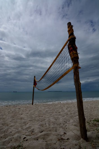 Volleyball net on sandy beach against cloudy sky