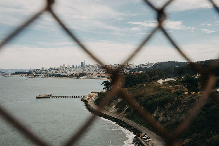 San Francisco San Francisco Bay California California Coast Architecture Cityscape Fence Looking Through Fence Built Structure Water Building Exterior No People Sky Focus On Background Nature City Travel Destinations Transportation Outdoors