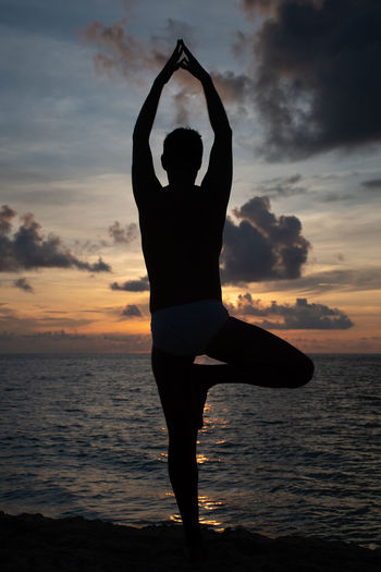 Silhouette yoga man standing at beach against sky during sunset