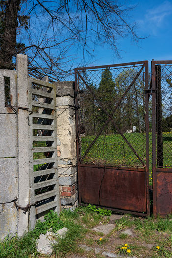 old fence elements, Castle Polish Krawarn, Poland Krowiarki Poland Fence Elements Plant Architecture Tree Built Structure Nature No People Day Entrance Safety Security Sky Gate Protection Fence Building Exterior Building Outdoors Boundary Open Barrier