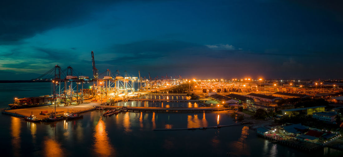 Illuminated harbor against sky at night