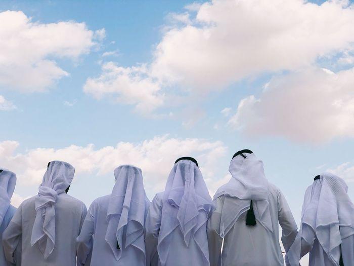 Arabic men from behind in kandora /thawb- traditional dress.