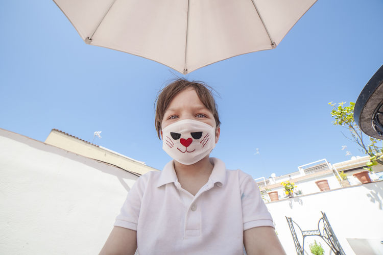 Low angle view of boy wearing mask against clear sky