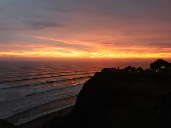 Sunset over Lima Escape Summer Surf EyeEm Selects Sunset Beauty In Nature Nature Scenics Orange Color Tranquil Scene Tranquility Beach Sky Horizon Over Water Idyllic Sea Travel Destinations Silhouette Cloud - Sky Outdoors No People