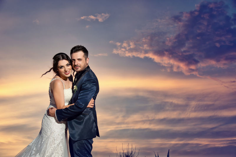 Adult Bonding Cloud - Sky Couple - Relationship Emotion Heterosexual Couple Love Men Outdoors Positive Emotion Real People Sky Standing Sunset Togetherness Two People Wedding Dress Women Young Adult Young Men Young Women