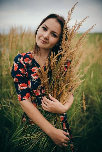 Portrait of woman holding crops while standing on field