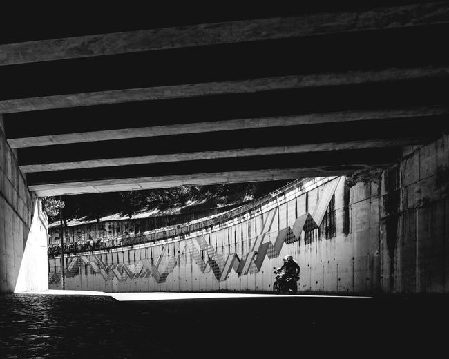 Silhouette person walking on bridge in city