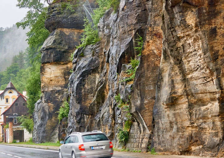 Cars moving on rock with mountain in background