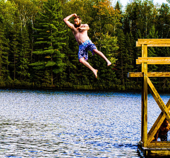 Mid adult man diving into lake