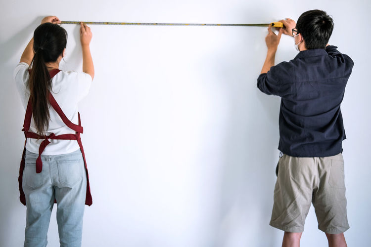 Rear view of man and woman measure wall with tape at home
