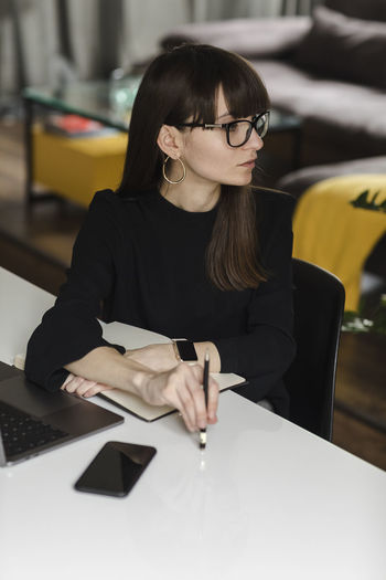 Business Adult Business Business Finance And Industry Business Person Businesswoman Businesswomen Front View Glasses Hairstyle Indoors  Office One Person Real People Sitting Table Wireless Technology Women Young Adult Young Women