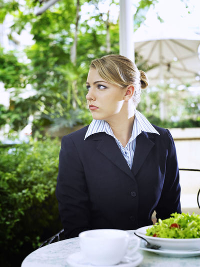 Thoughtful Businesswoman Looking Away While Sitting By Table