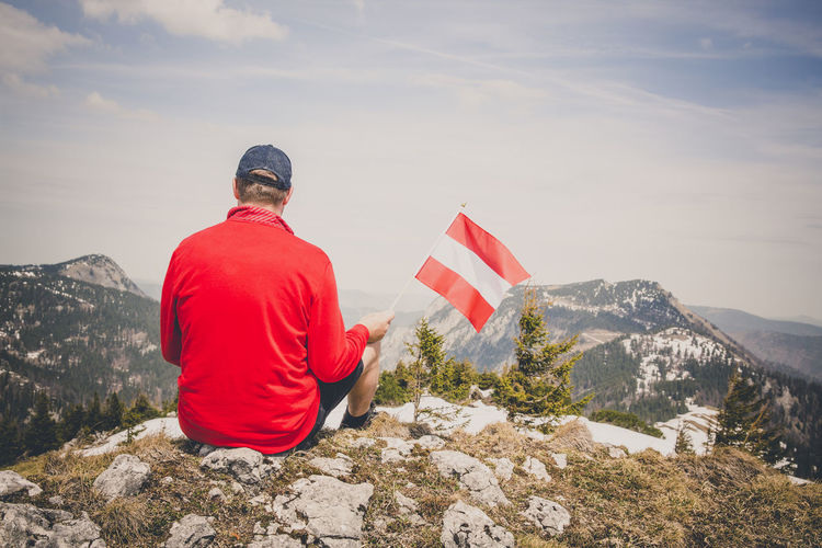 hiker with red sweater is holding an austria flag in the mountains Beauty In Nature Day Flag Freedom Leisure Activity Lifestyles Mountain Mountain Peak Mountain Range Nature One Person Patriotism Real People Rear View Red Scenics - Nature Sitting Sky Tranquil Scene Tranquility