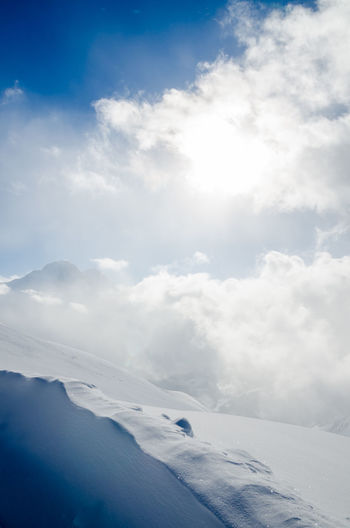 Scenic view of snowcapped mountains with bright light through clouds against sky
