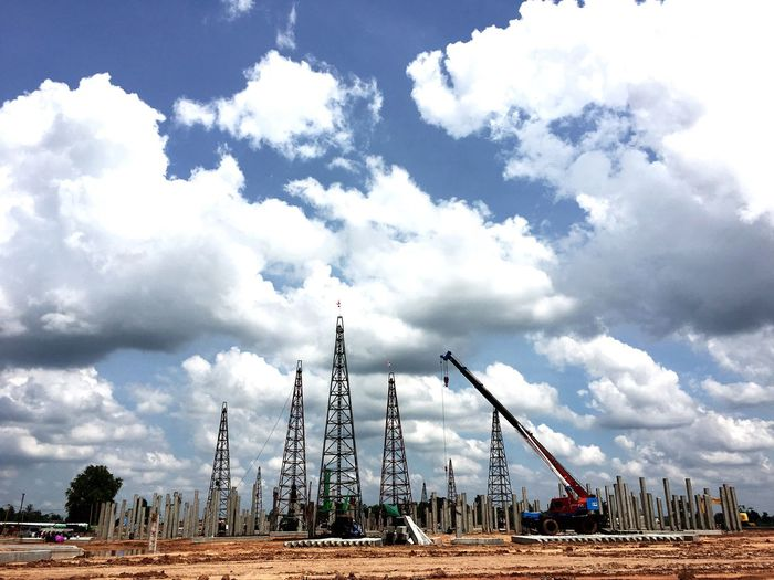 Cranes at construction site against cloudy sky