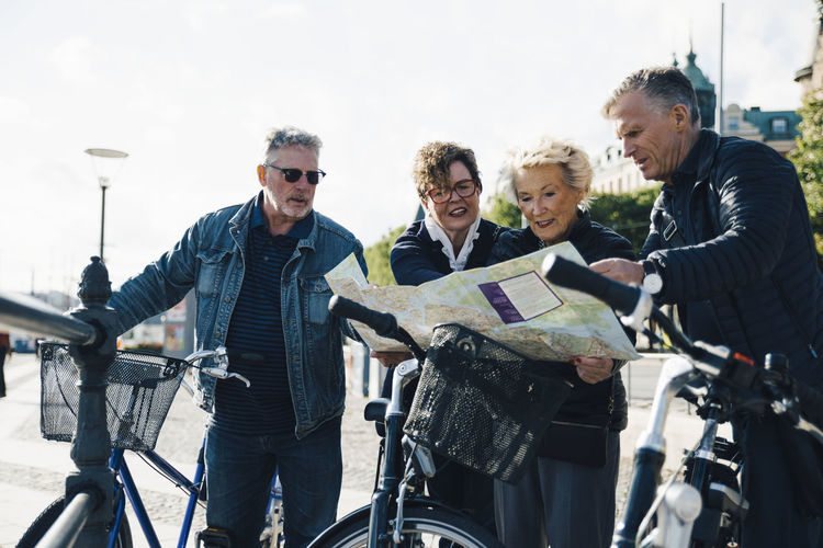 Senior male and female friends with bicycles reading map in city