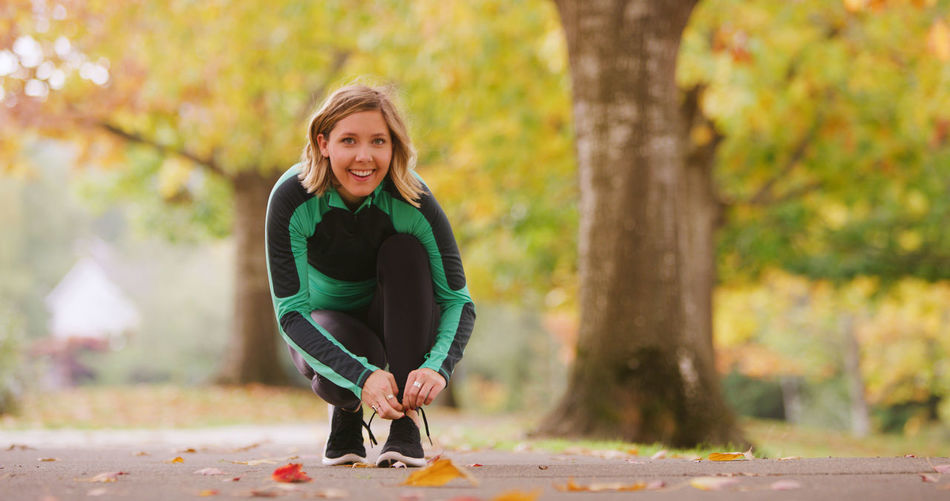Smiling young woman tying shoelace in park during autumn