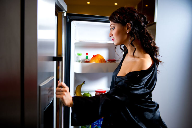 Sensuous woman wearing black bathrobe looking in refrigerator at home