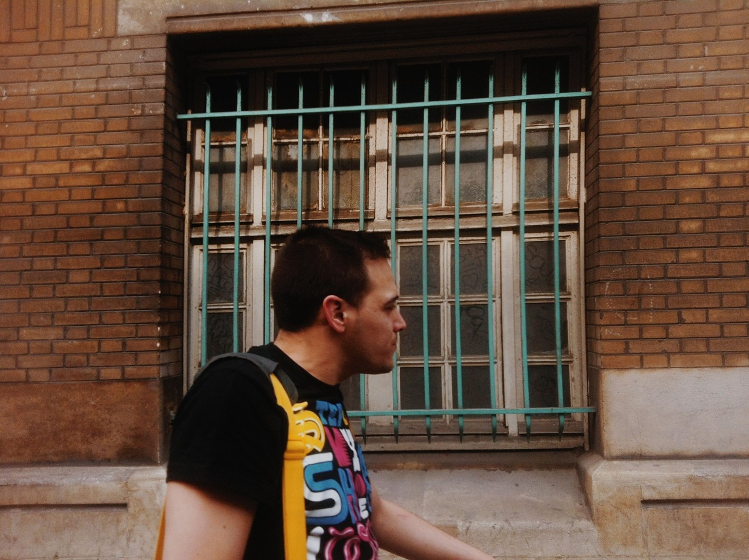 building exterior, architecture, built structure, person, young adult, lifestyles, front view, leisure activity, portrait, window, looking at camera, casual clothing, brick wall, standing, young men, building, smiling