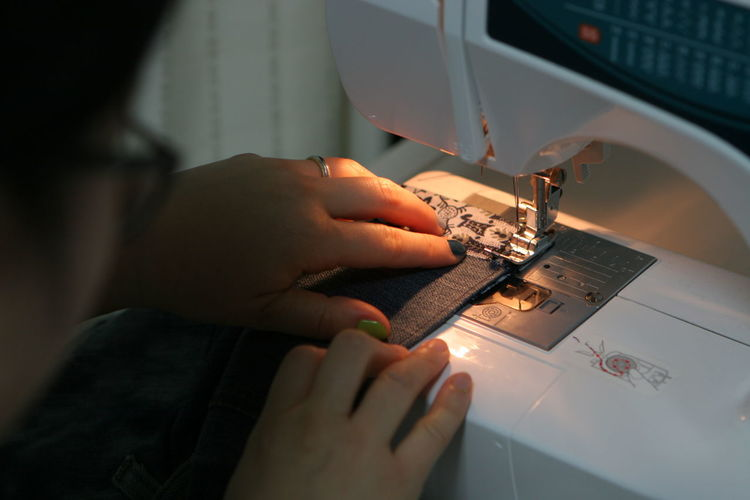 High angle view of woman working with fabric on sewing machine