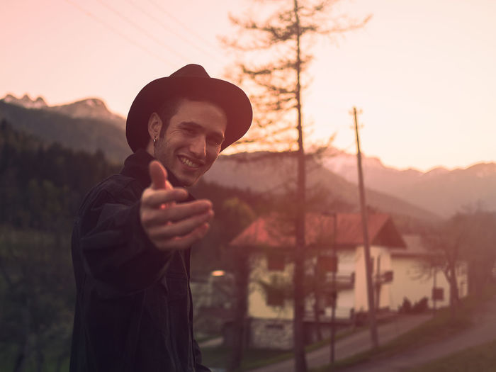 Portrait Of Smiling Young Man Gesturing While Standing Against Houses And Mountains
